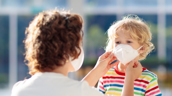 Mother putting mask on young child