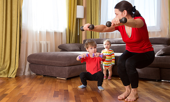 Woman exercising at home with two small children next to her