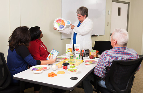 instructor standing in front of three people explaining food-related information