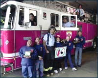 Photo of kids standing with a fireman in front of fire truck