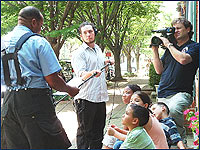 Photo of a cameraman recording a man speaking to kids