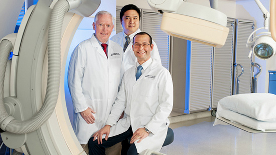 Cardiologists Dr. Jeffrey Etherton, Dr. Benjamin Remo, and Dr. Gabriel Sardi are pictured in the Cardiac Cath Lab around medical equipment.