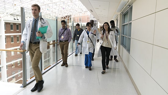 UMMC residents walking through a hospital hallway with physician leadership