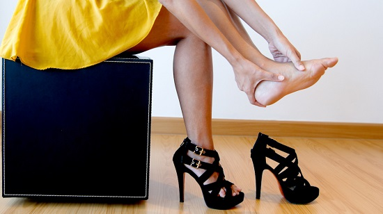 Woman in high heels rubbing her foot - Neuroma foot pain